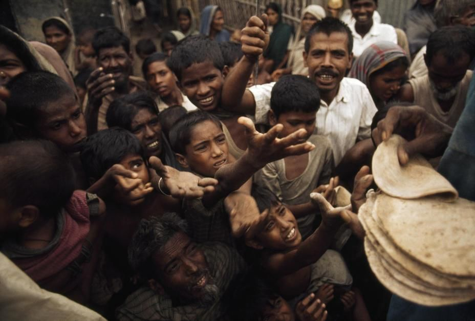 Starving Bengalis reach for bread at a Red Cross feeding kitchen. [Fotografija dneva - julij 2011]