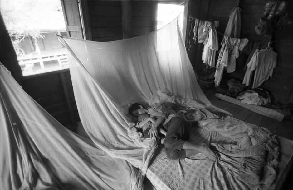 Mother and daughter snuggle together in bed while laundry hangs to dry. [Photo of the day - יולי 2011]