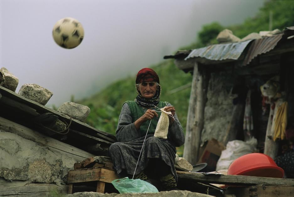 A soccer ball flies over the head of a woman who is knitting outdoors. Turkey. [Dagens foto - augusti 2011]