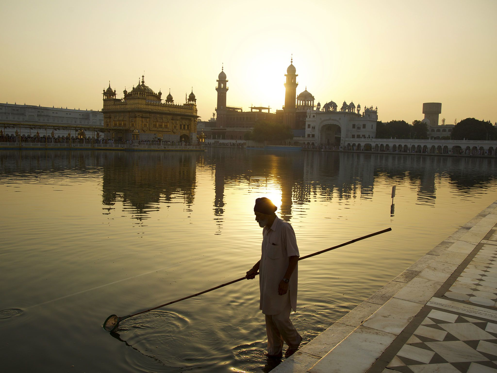 Punjab, India: A man cleans the moat as the sun rises at the Golden Temple. This image is from... [Photo of the day - May 2017]