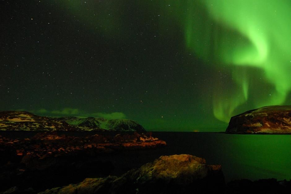 Norveka: Severni sij (Aurora borealis) je nebo obarvala nebo in vodo v neonsko zeleno barvo. Pr... [Fotografija dneva - marec 2012]