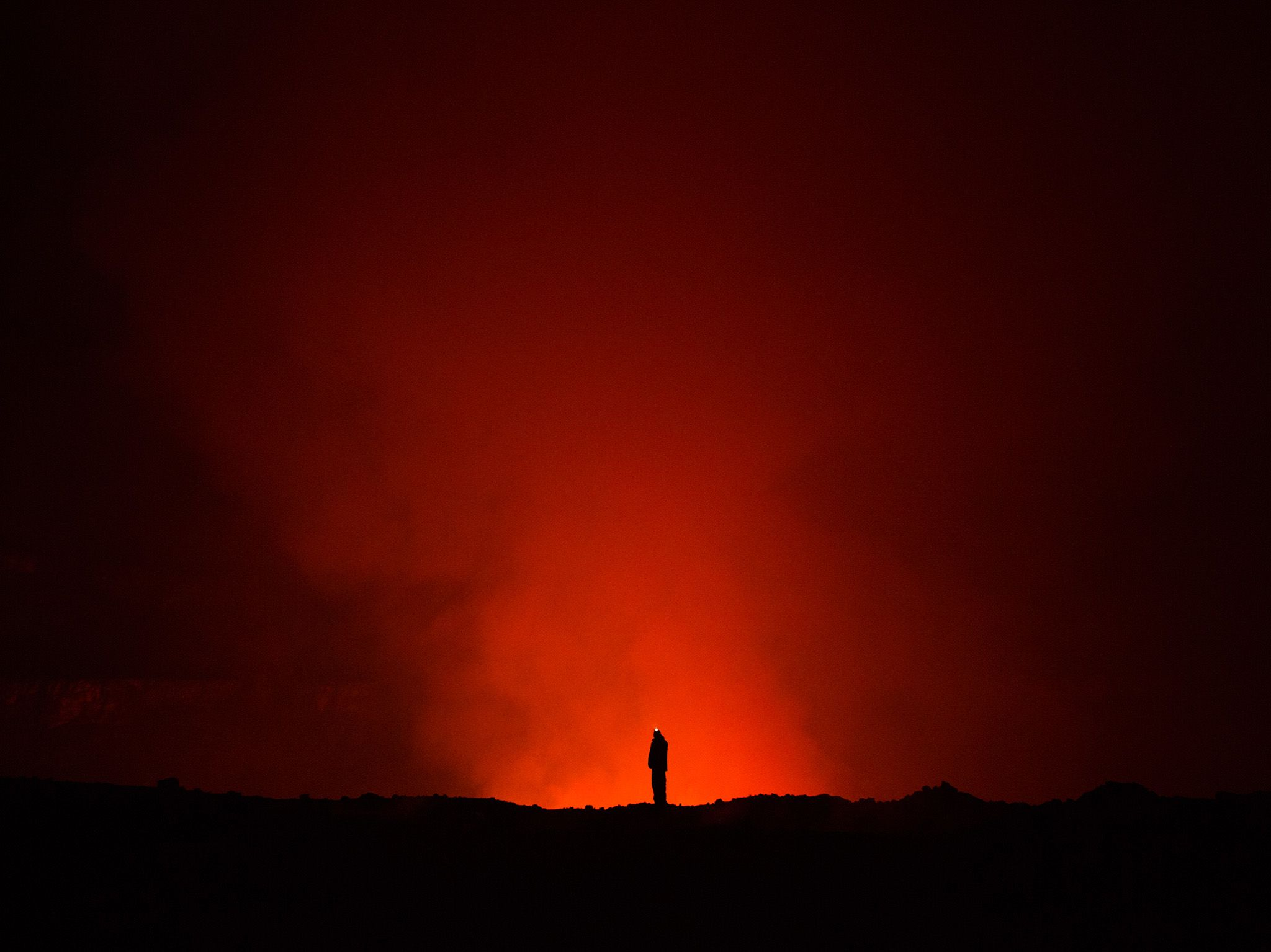 Prof. Ken Sims of the University of Wyoming looking over a lava crater at Mount Nyiragongo. Lava... [Photo of the day - March 2018]
