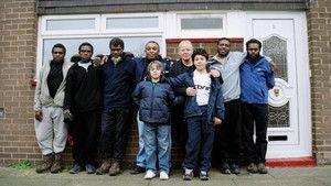 De indfødte kommer til byen i England Billed